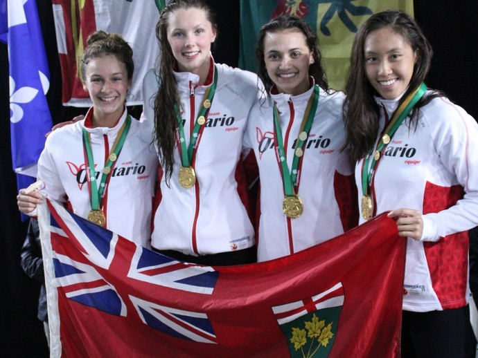 Kylie Masse (second from right) standing with her three other teammates, all smiling and holding an Ontario flag after winning a gold medal.