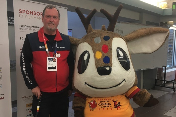 Paul Hébert grabs a photo with the mascot of the 2019 Canada Winter Games, Waskasoo