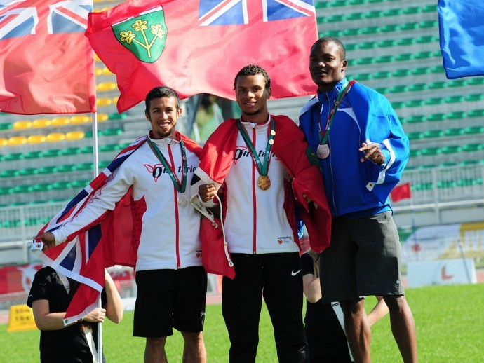 Andre De Grasse standing on top of the podium, between other medal winners, with an Ontario flag draped around his shoulders and his gold medal around his neck.