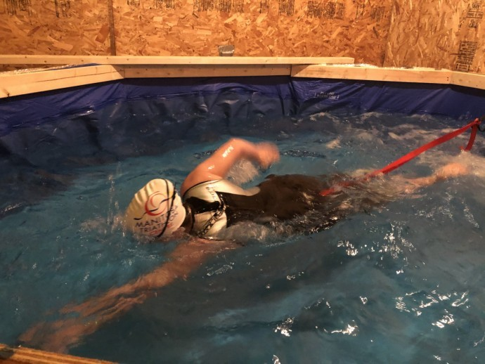 Megan swimming, while tethered in place, in the training pool that her parents built for her in the family's garage