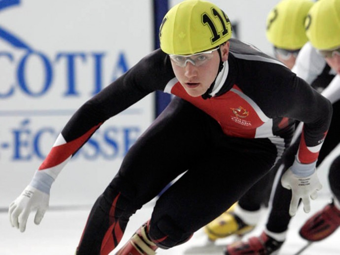 Vincent de Haitre crouches down low while rounding a corner during the short track speed skating competition.