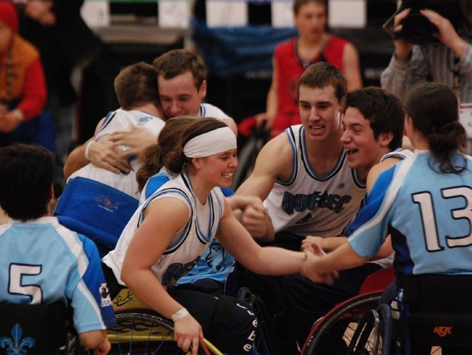 Cindy Ouellet is grinning while clasping the wrist of another teammate while other teammates celebrate in the background after winning gold in wheelchair basketball.