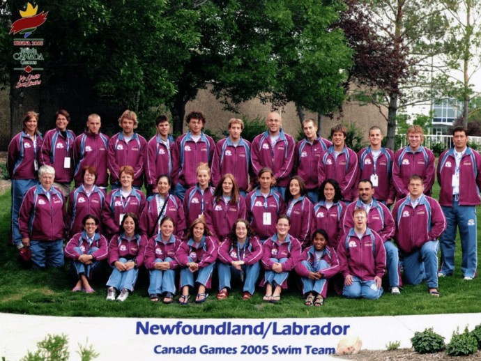 Katarina Roxon in her provincial swimming team photo with three rows of people, all wearing their purple and blue jackets with blue pants outside on the grass in front of some trees.
