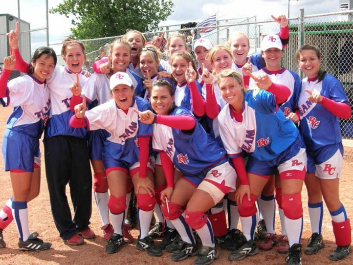 Jennifer Salling and Danielle Lawrie stand in a group photo on the softball field with their teammates, all smiling and holding up their index fingers to indicate number one.