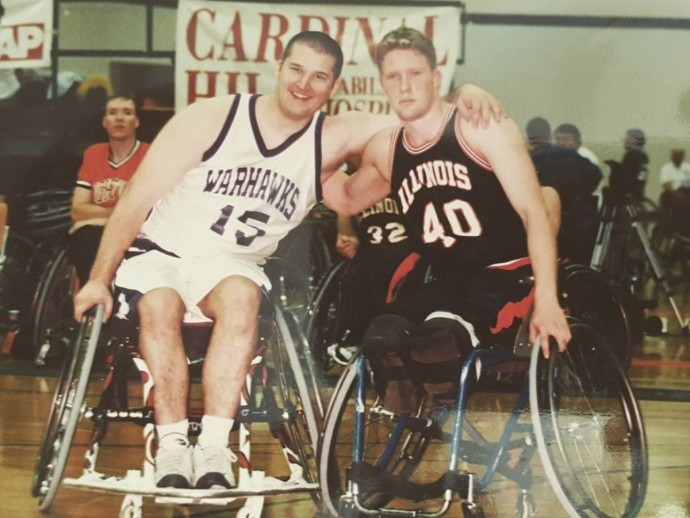 Patrick Anderson (on the right) is posing for a picture with his arm around a competitor on a wheelchair basketball court.